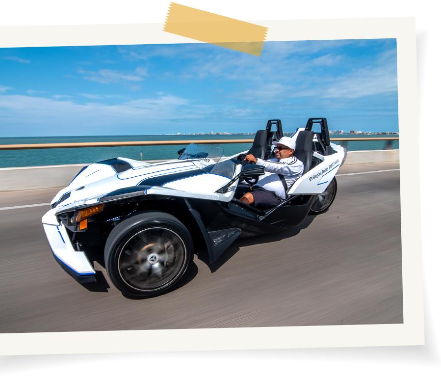 Driver riding slingshot through South Padre Island coastline